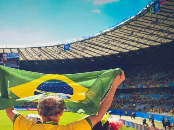 Homem mais velho segurando uma bandeira do Brasil em estádio cheio para a Copa do Mundo